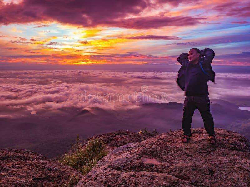 Podróżnika stojak na Skalistym cilff z sunsire niebem i piękny obłoczny morze na «Pa na raja «Khao Luang mountian obraz royalty free