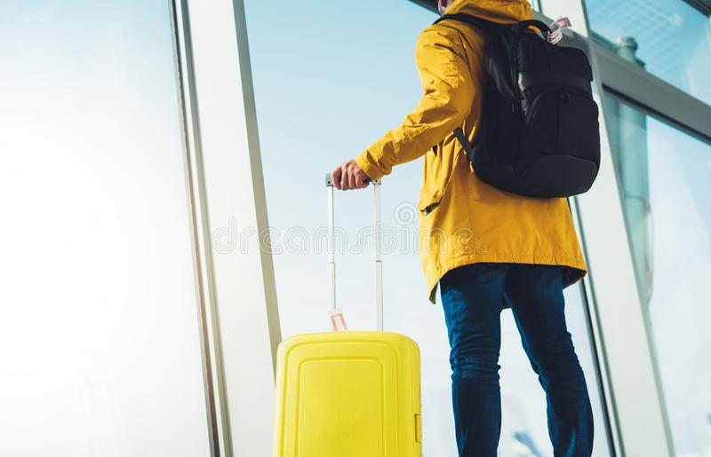 Podróżnika turysta z żółtym walizka plecakiem stoi przy lotniskiem na tła wielkim okno, mężczyzna w jaskrawym kurtki czekaniu zdjęcie stock
