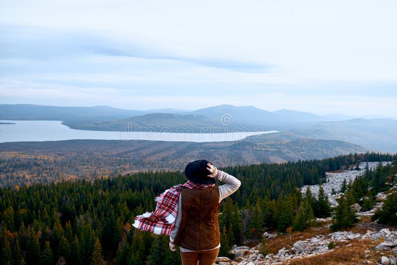 podróżomanii i podróży pojęcie Podróżnik kobieta w kapeluszowych patrzeje górach Wycieczkować na górze atmosferyczny moment zdjęcia stock