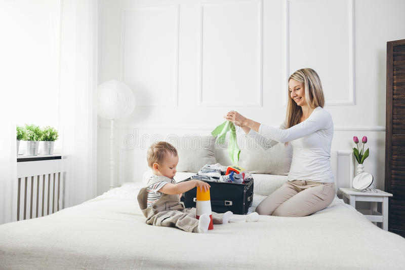 Podróżować z dzieciakami Szczęśliwa matka z jej dziecka kocowaniem odziewa dla wakacje fotografia stock