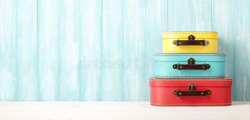 Podróżuje pojęcie z retro stylowymi walizkami na błękitnym drewnianym backgro fotografia royalty free