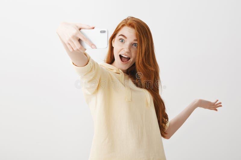 Podróży blogger pokazuje ona zwolenników zwiedza robić online przekładowi z smartphone Z podnieceniem dziewczyna z czerwienią fotografia royalty free