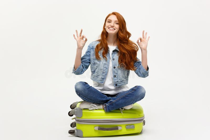 Podróży i stylu życia pojęcie: Młody caucasian kobiety obsiadanie na walizce i seansu ok palec podpisujemy Odizolowywający na bie zdjęcia royalty free