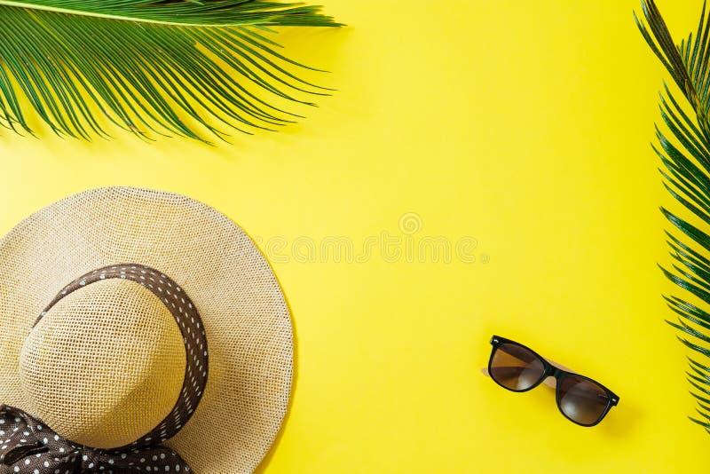 Podróży pojęcie: kapelusz, palmowy liść i słońc szkła na żółtym backgro, fotografia stock