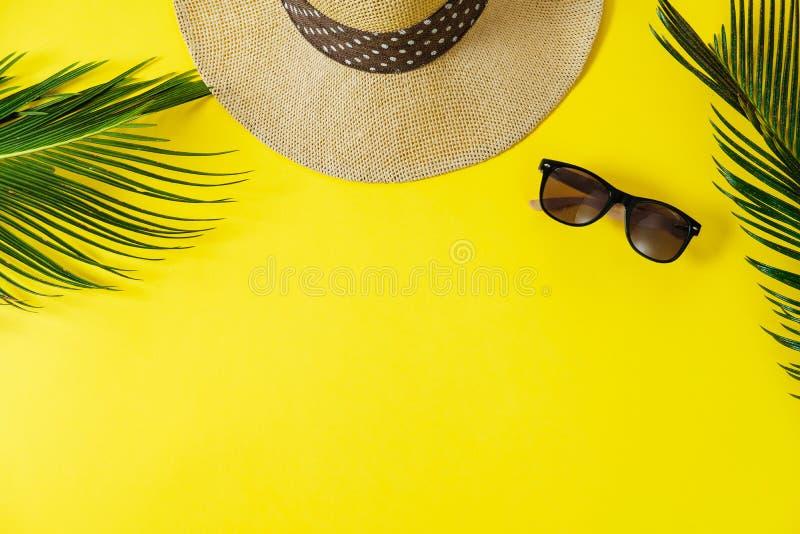Podróży pojęcie: kapelusz, palmowy liść i słońc szkła na żółtym backgro, zdjęcia stock