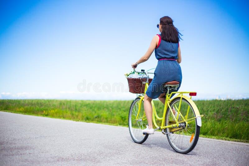 Podróży pojęcie - tylny widok kobieta rocznika jeździecki bicykl z fotografia stock