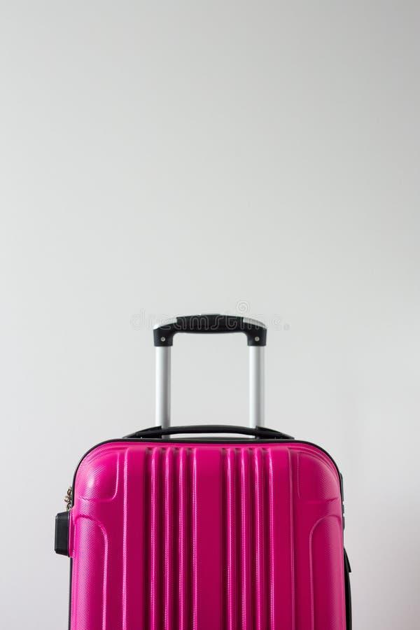 Podróży tło - różowa plastikowa walizka nad białym tłem z kopii przestrzenią zdjęcie royalty free