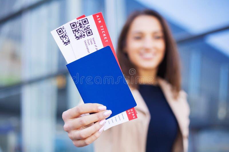 Podr?? Kobieta trzyma dwa lotniczego bilet w zagranicy paszportowym pobliskim lotnisku zdjęcie stock