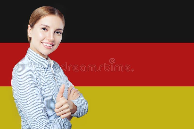 Podr?? w Niemcy poj?ciu Ładny busineswoman pokazuje kciuk w górę Niemcy flagi tła przeciw zdjęcia stock