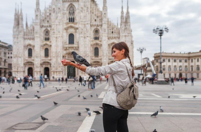 Podr??y turystyczna kobieta karmi go??bki blisko Duomo di Milano - katedralny ko?ci?? Mediolan w W?ochy Dziewczyna cieszy si? na  zdjęcia royalty free