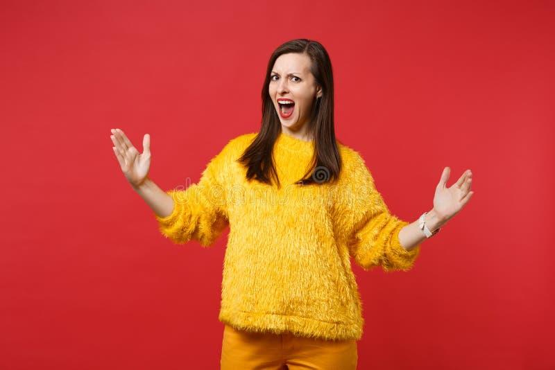 Podrażniona młoda kobieta krzyczy gestykulować w żółtym futerkowym pulowerze demonstrujący rozmiar z horyzontalnym workspace odiz fotografia royalty free
