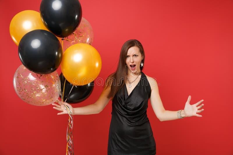 Podrażniona młoda kobieta w czerni sukni odświętności przysięganiu, podesłanie wręcza trzymać lotniczych balony odizolowywa na cz fotografia royalty free