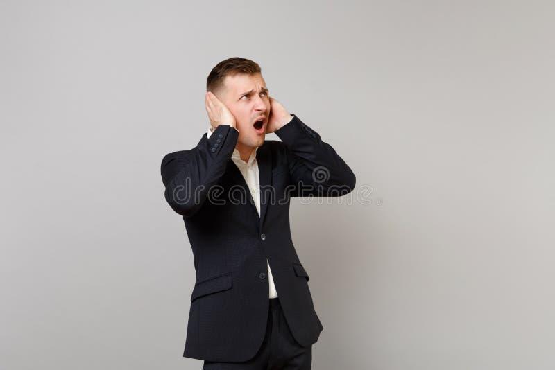 Podrażniony młody biznesowy mężczyzna w klasycznego czarnego kostiumu nakrywkowych ucho z rękami, przyglądającymi w górę, przysię obrazy stock