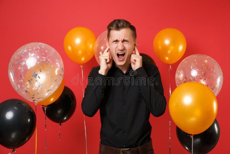 Podrażniony młody człowiek w czarnych klasycznych koszulowych nakrywkowych ucho z palcami na czerwonego tła lotniczych balonach S fotografia stock