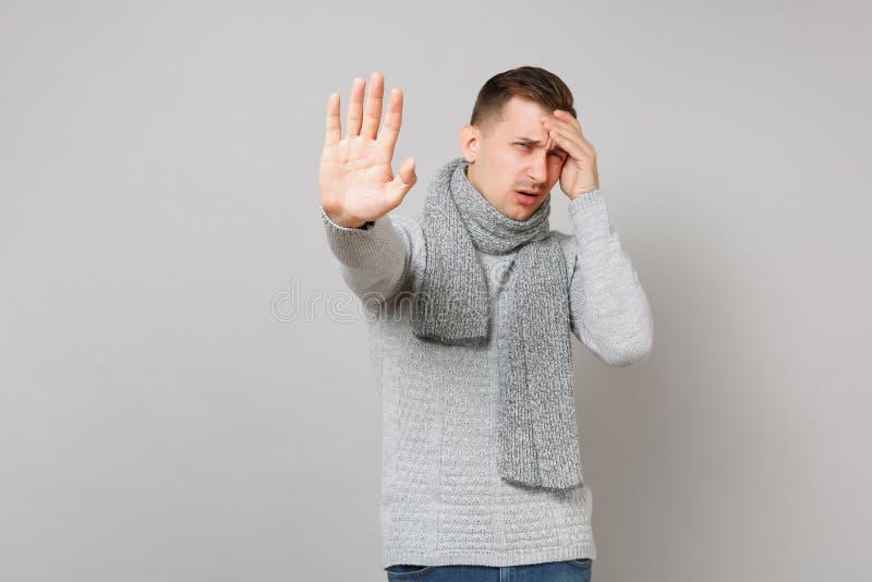 Podrażniony młody człowiek w szarym pulowerze, szalika nakrycie ono przygląda się z ręką, seans przerwy gest z palmą na popielaty fotografia royalty free