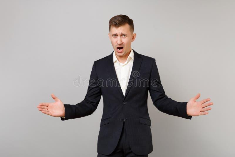 Podrażniony uwłaczający młody biznesowy mężczyzna w klasycznym czarnym kostiumu, koszulowe podesłanie ręki, utrzymuje usta szerok fotografia stock