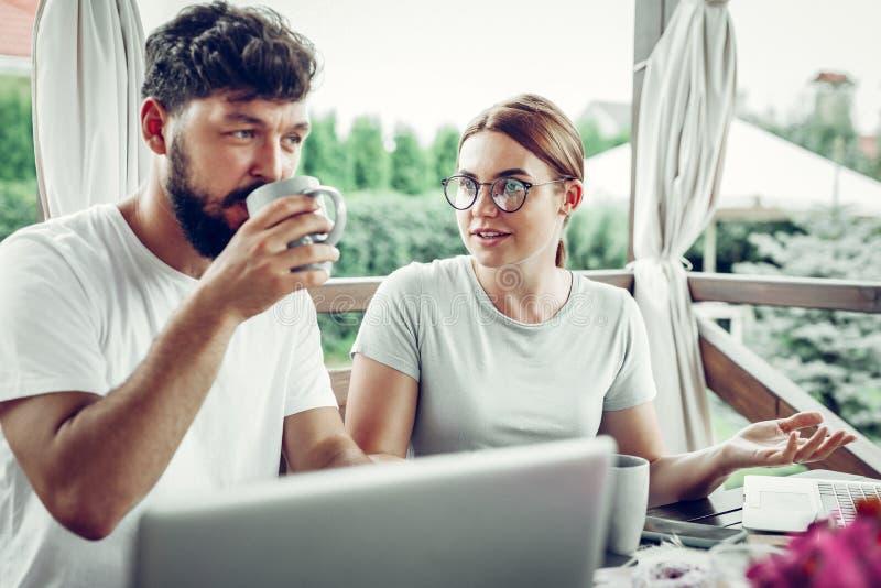 Podrażniona dama mówi współmałżonek podczas gdy pije kawę zdjęcie stock