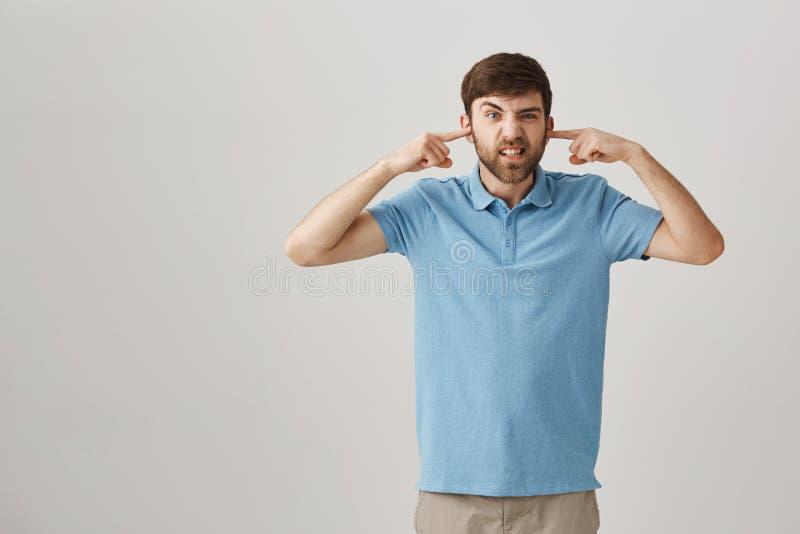 Podrażniona i zmieszana atrakcyjna samiec z nakrywkowymi ucho z palcami wskazującymi, dokuczający z obraz stock
