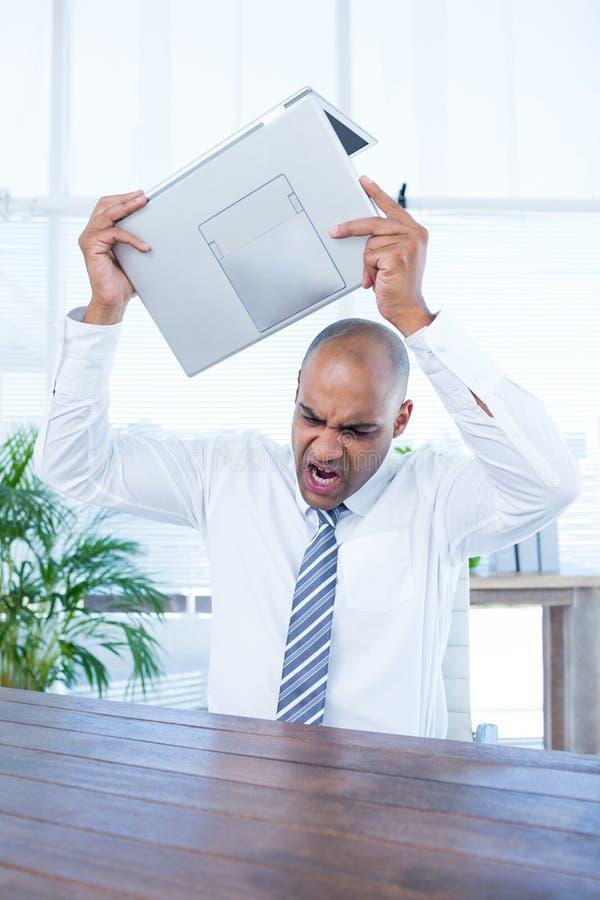 Podrażniony biznesmen łamać jego laptop wokoło zdjęcie royalty free