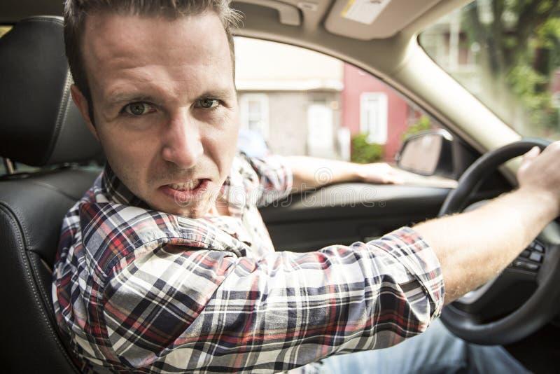 Podrażniony młody człowiek jedzie samochód Podrażniony kierowca obrazy stock