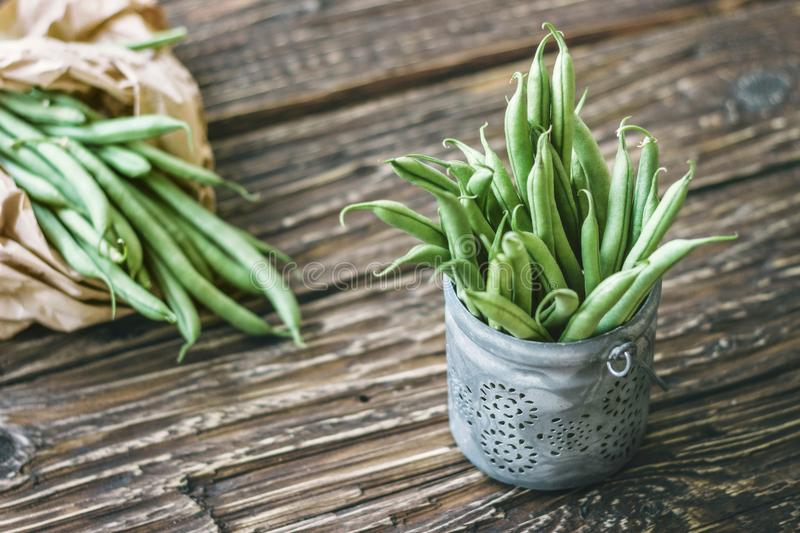 Pods of fresh organic green beans in paper bag and in a bowl on stock photography