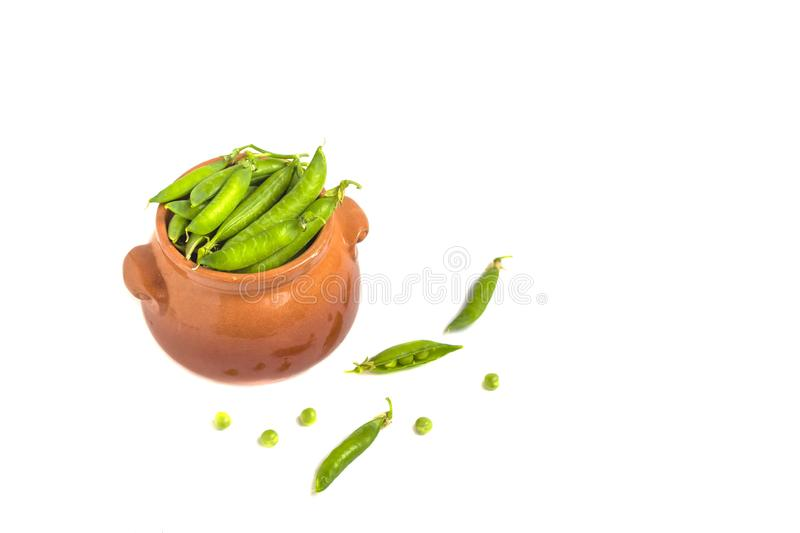 Pods of green peas and pea in a clay pot isolated on a white. The concept of vegetarian food. Organic foods and fresh vegetables stock photos