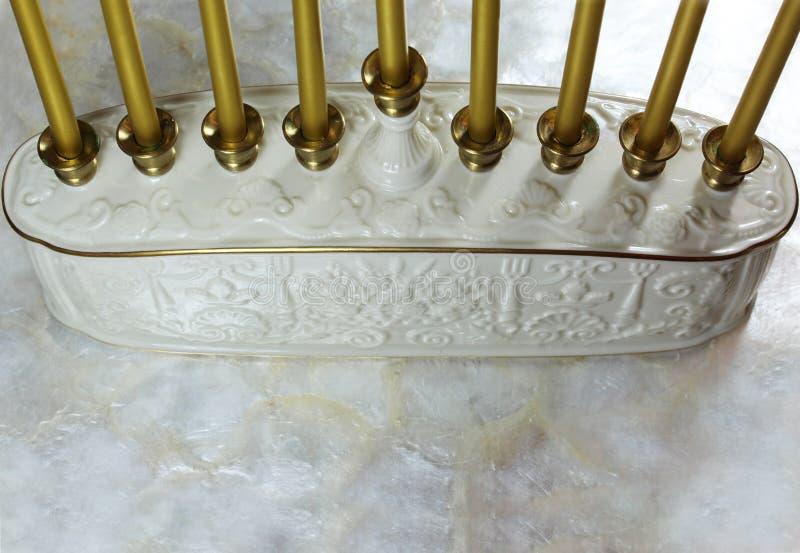 Podstawowe i złociste świeczki ceramiczny Hanukkah menorah na miękkim białym tle fotografia stock