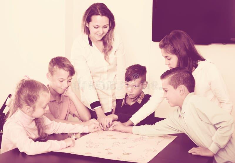 Podstawowi pełnoletni radośni dzieci przy stołem z grze planszowa i kostka do gry fotografia royalty free