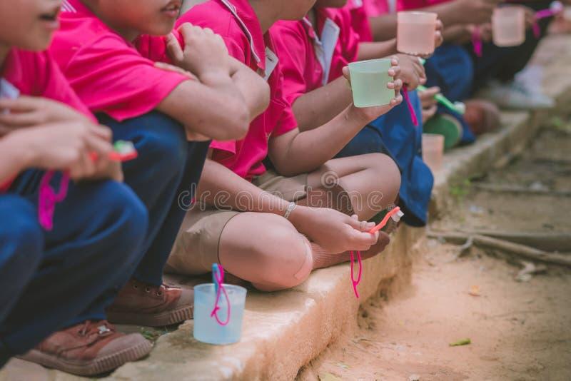 Podstawowi ucznie szczotkują ich zęby po lunchu obraz stock