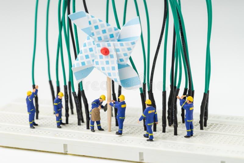 Podtrzymywalna energia, alternatywny czysty eco władzy pojęcie, miniaturowi ludzie pracownik pomocy budynku wiatraczka elektryczn fotografia royalty free