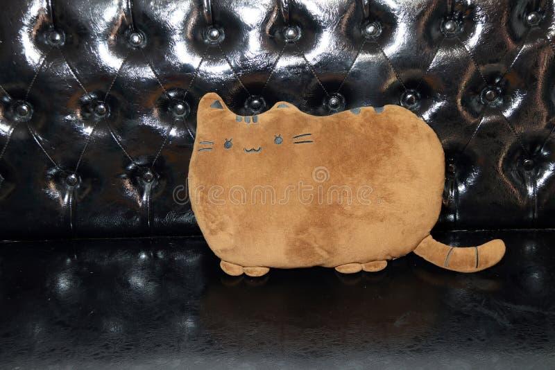 Poduszka kształt kot w brown kolorze na czarnej rzemiennej kanapie poduszka jest sukiennym torbą faszerującym z piórkami zdjęcia stock