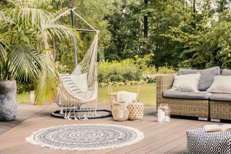 Poduszki na hamaku na tarasie z round dywanika i rattan kanapą wewnątrz zdjęcia stock