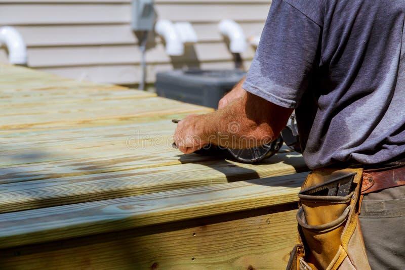 Podwórka pokładu odbudowy mężczyzna przystojny cieśla instaluje drewnianego podłogowego nowego dom obraz stock