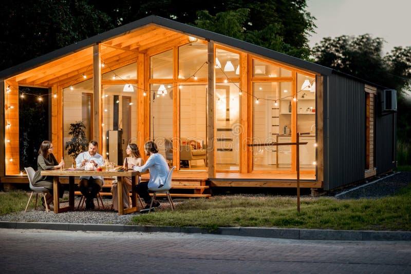 Podwórko dom z ludźmi siedzi przy stołem fotografia stock