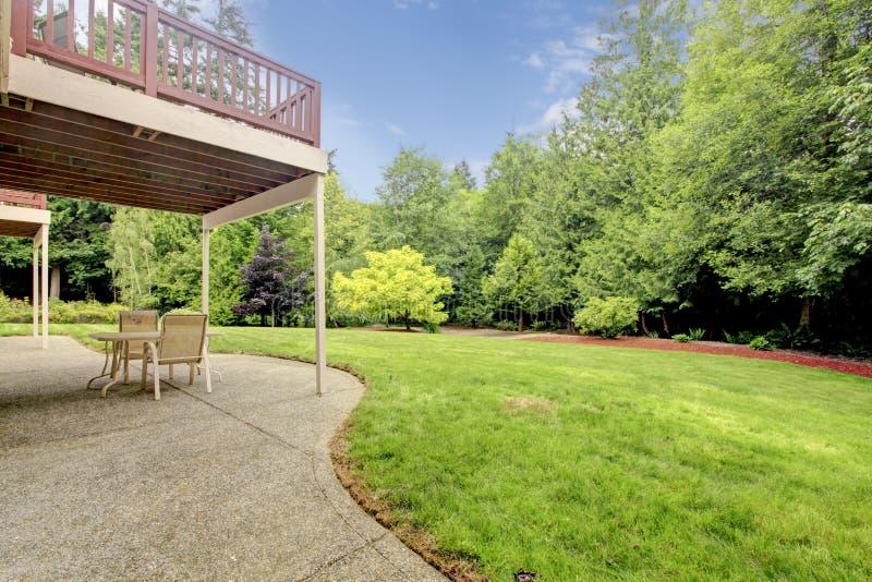 Podwórze houes z ganeczkiem i zieleni lasem. fotografia stock