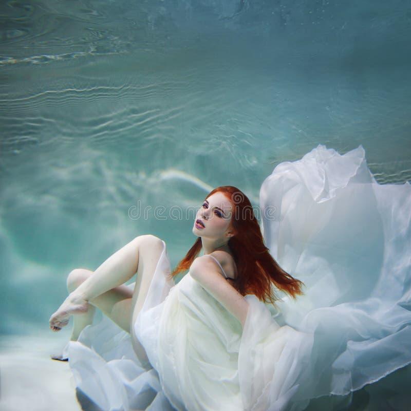 Podwodna dziewczyna Piękna miedzianowłosa kobieta w białej sukni, pływa pod wodą obrazy royalty free