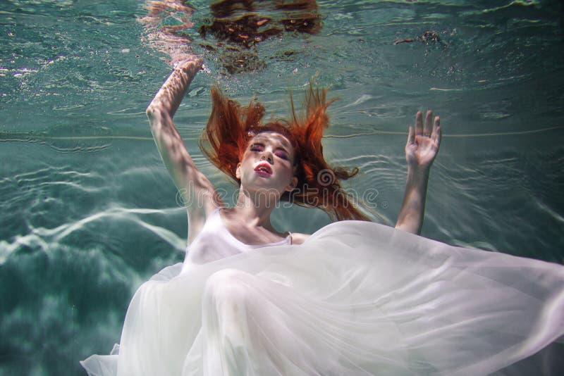 Podwodna dziewczyna Piękna miedzianowłosa kobieta w białej sukni, pływa pod wodą obraz stock