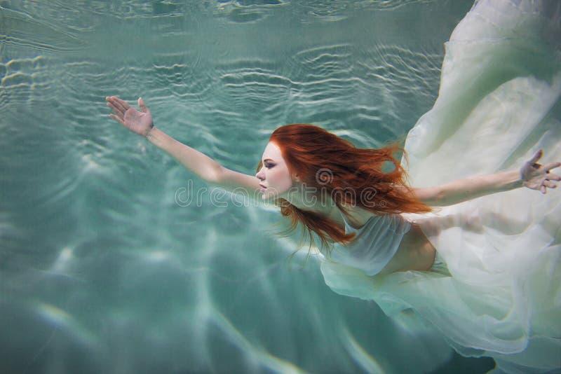 Podwodna dziewczyna Piękna miedzianowłosa kobieta w białej sukni, pływa pod wodą fotografia royalty free