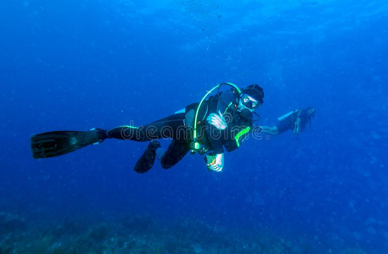 Podwodna scena z zamarzniętym akwalungu nurkiem trzyma skorupę fotografia royalty free