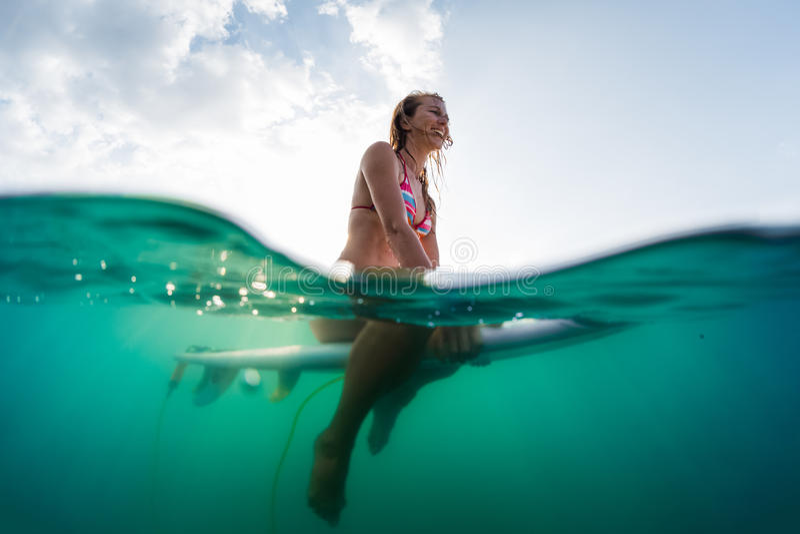 Podwodny widok szczęśliwy kobiety obsiadanie na surfboard zdjęcie stock