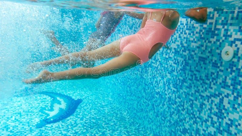 Podwodny wizerunek dwa nastoletniej dziewczyny nurkuje i p?ywa podwodny przy basenem zdjęcia stock
