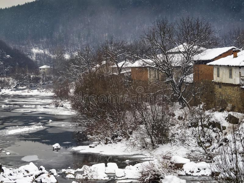 Podwyższony śnieżny zimy wioski widok od mostu starzy riverbank domy i rzeka fotografia royalty free