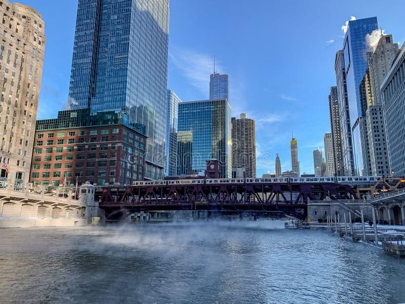 Podwyższony pociąg krzyżuje marznie Chicagowską rzekę gdy kontrpara wzrasta podczas gdy temperatury gwałtownie spadać obraz royalty free