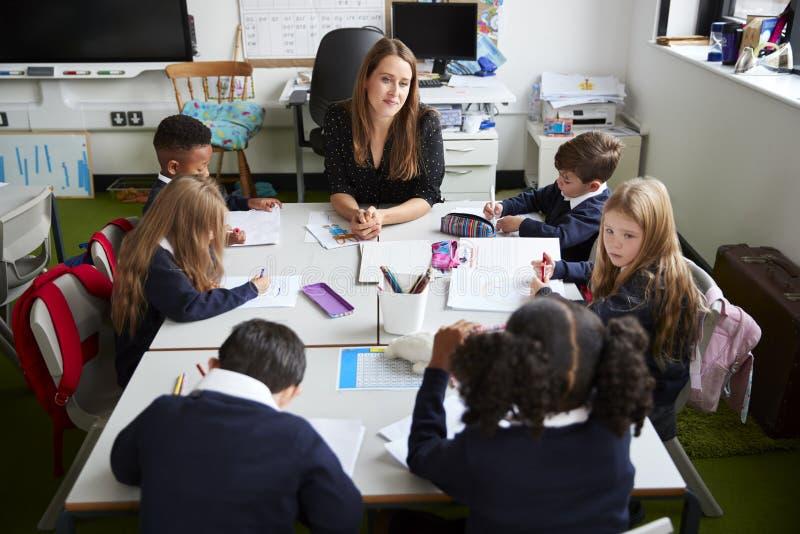 Podwyższony widok żeński szkoła podstawowa nauczyciela obsiadanie przy stołem w sali lekcyjnej z uczniami podczas lekcji obrazy royalty free