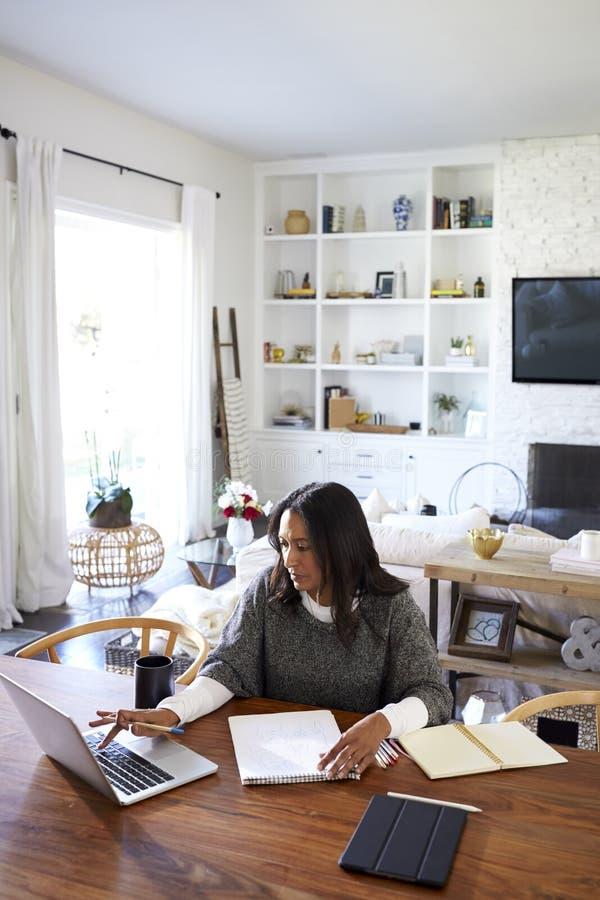 Podwyższony widok pionowo w średnim wieku amerykanin afrykańskiego pochodzenia kobiety obsiadanie przy stołem w jej jadalni używa obrazy stock