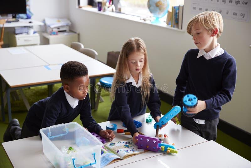 Podwyższony widok trzy szkoła podstawowa dzieciaka stoi przy stołem w sali lekcyjnej, pracuje wraz z zabawkarskimi budowa blokami zdjęcie royalty free