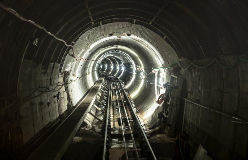 Podziemnej kopalni jamy tunelowa galeria z pracującymi liniami kolejowymi zdjęcia royalty free