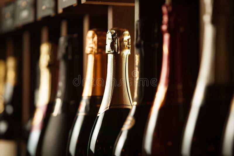 Podziemny loch z elity iskrzastym winem na półkach, zakończenie w górę horyzontalnej fotografii obrazy stock
