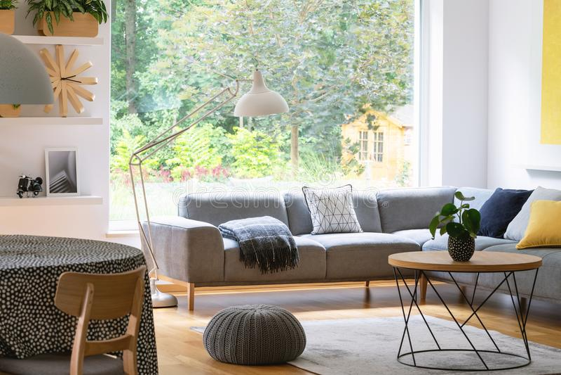 Poef naast lijst in modern woonkamerbinnenland met grijs graan royalty-vrije stock foto's