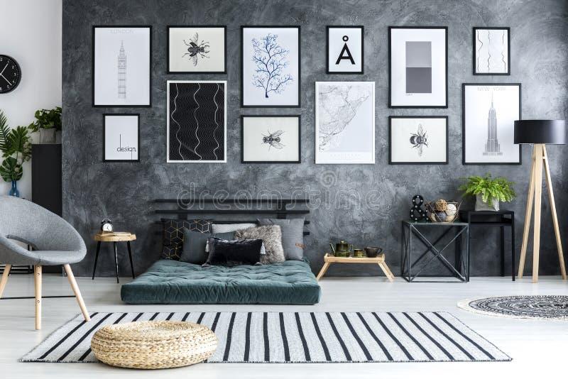 Poef op gestreepte deken in grijs woonkamerbinnenland met galerij van stock afbeelding